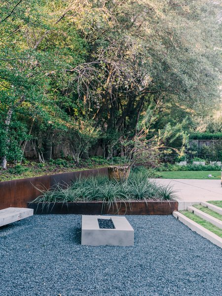 Behind her is the greenhouse, where Lynn starts vegetables like lettuce, Swiss chard, and tomatoes. Landscape architect David Hocker defined the sunken fire pit area with Cor-Ten steel.