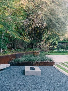 A Black Stucco Home in Dallas Is Surrounded by Eye-Popping Greenery - Photo 2 of 17 - Landscape architect David Hocker defined the sunken fire pit area with Cor-Ten steel.