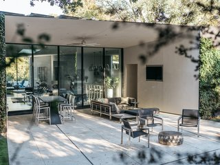 """A Black Stucco Home in Dallas Is Surrounded by Eye-Popping Greenery - Photo 4 of 17 - Carved into the home's mass are what Ong calls """"exterior voids"""": transition zones between the built and the natural that are painted white. The sectional and club chairs are from Kingsley Bate; the sliding glass door is by Western Window Systems."""