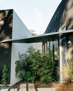 """A Black Stucco Home in Dallas Is Surrounded by Eye-Popping Greenery - Photo 5 of 17 - The entrance to the house is marked by a triangular awning. """"It's just enough to protect the front door,"""" says Merrill, """"and then it sheds water into a small garden between the garage and the house."""""""