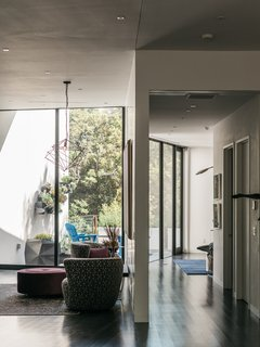 A Black Stucco Home in Dallas Is Surrounded by Eye-Popping Greenery - Photo 7 of 17 - A sitting area off the main living space features chairs upholstered by Berkeley Fabrics & Upholstery and a light fixture from Lights Fantastic.
