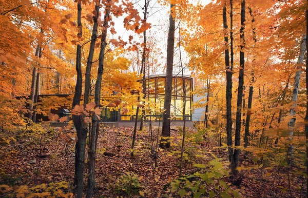 """Clad in SPF lumber, zinc, and glass, David Bronskill and Mark Dilworth's vacation home on Oblong Lake fans out to capture wide views of the forest. """"Nothing is straight in the plan,"""" says architect Roland Rom Colthoff of RAW Design, who conceived the 2,500-square-foot escape. From left to right, there are three structures: a three-bedroom guest wing, a voluminous communal area, and a semi-detached master suite. Two of the wings share an unusual fin-shape design because of their varied ceiling heights."""