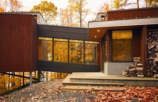 A Curved House in Ontario Bends 100 Degrees For Forest Views - Photo 3 of 16 - Set on a steel frame and reached by a bridge, the master suite extends up to 13 feet above the sloping grade.