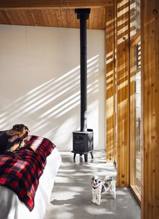 A Curved House in Ontario Bends 100 Degrees For Forest Views - Photo 7 of 16 - The master suite is warmed by a Badger 3112 woodstove by Morsø.