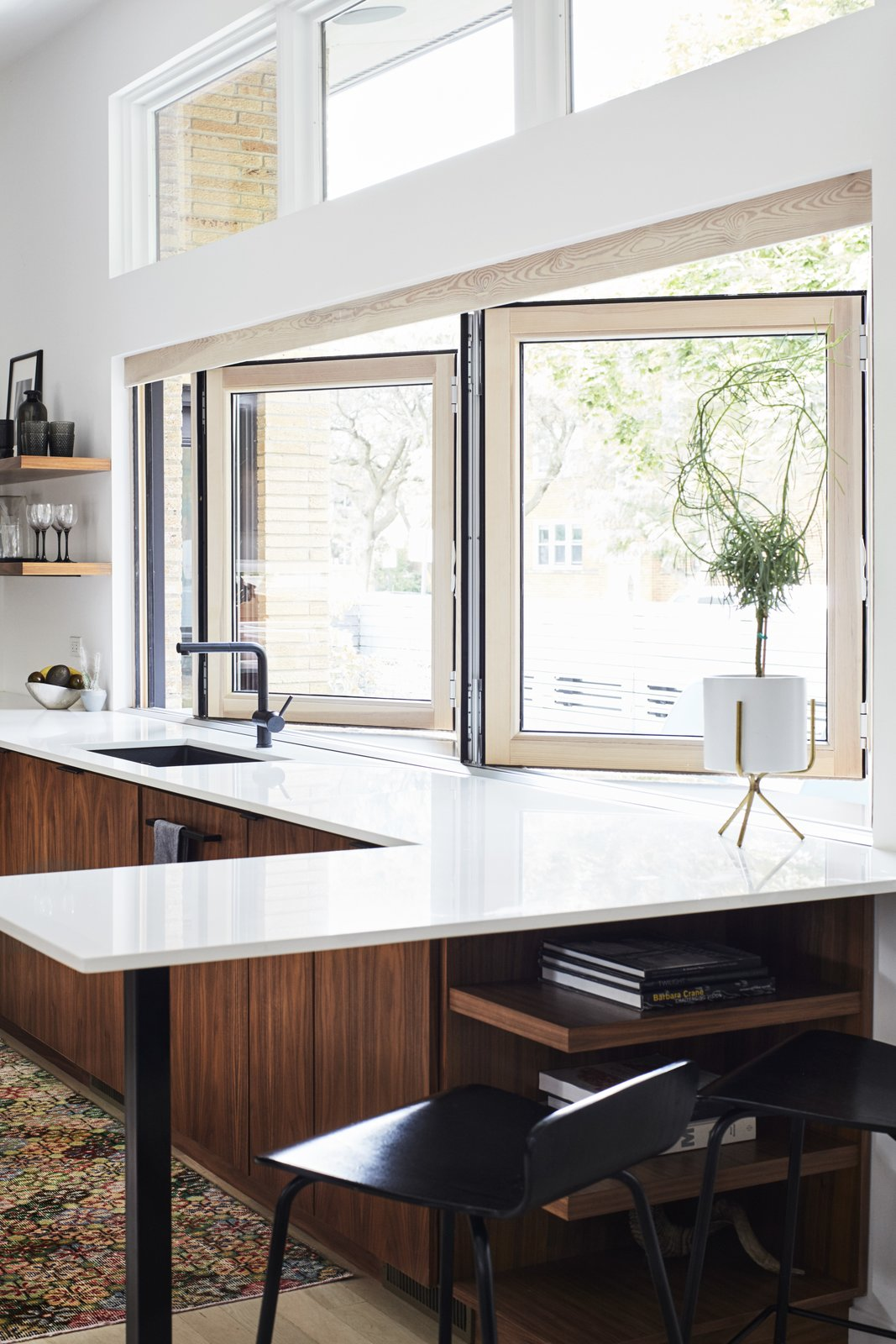 A 14-foot-wide opening defines the kitchen, which architect Scott Delano, with Nicholas Pettit, carved out of what had been an enclosed breezeway and part of the garage. The bifold window is from NanaWall, the windows above are by Pella, and  the faucet is by Blanco.
