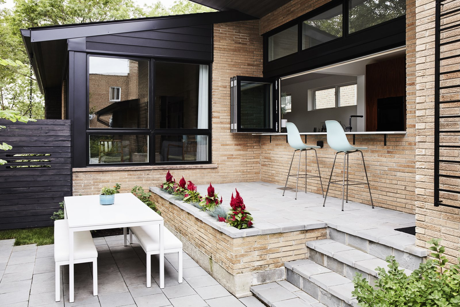 In the front courtyard, a raised bluestone patio was built off the new kitchen for casual meals and entertaining. The Eames Molded Plastic Chairs are from Herman Miller. The dining table and benches are from Room & Board.