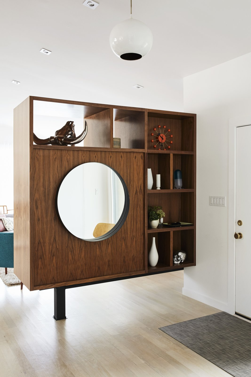 To break up the long living room, Pettit created a walnut bookcase at the entrance. Tagged: Storage and Shelves.  Best Storage Photos from Midcentury Mashup: A 1950s Ranch House in Chicago Gets a Palm Springs-Style Butterfly Roof