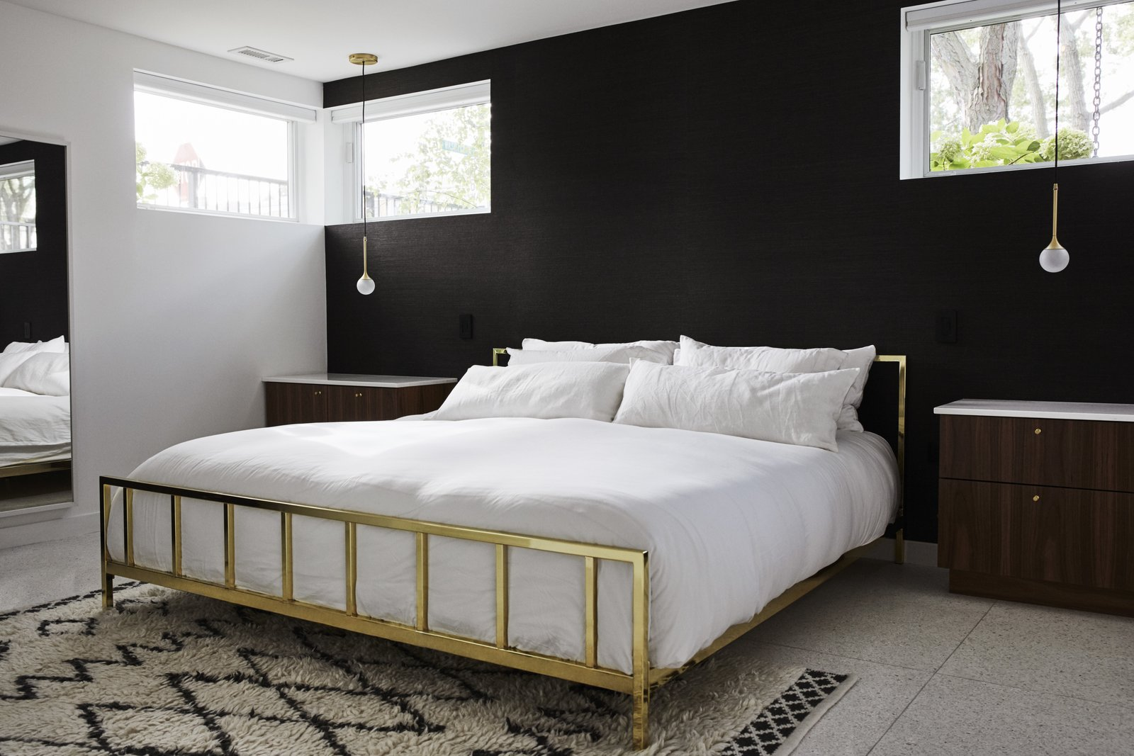 An Alchemy bed from CB2 is flanked by marble-topped night stands. The Krisztian Mecs for Intueri Light pendants are from Lumens.