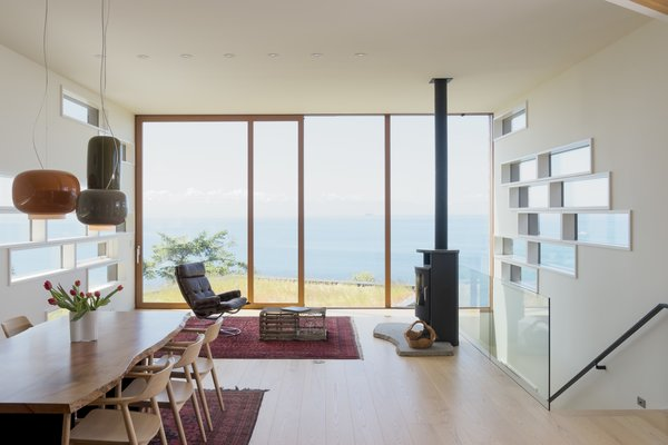 Lift-slide doors by Dynamic Windows allow easy access to planted rooftops that serve as small yards. The staggered rectangular panes, also by Dynamic Windows, reference the home's multilevel configuration.