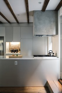 An Ad Copywriter Edits His Manhattan Row House—and Finds a New Calling - Photo 5 of 14 - The kitchen range hood is framed in wood, wrapped with cement board, and parged with a thin layer of polished concrete. The sides of the Carrara-topped island are clad in anodized aluminum, as are the IKEA cabinets.
