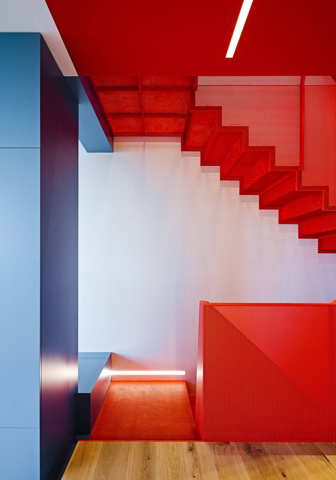 A perforated-metal staircase in Benjamin Moore's Flame and built-in cabinetry in various shades of blue highlight Fougeron Architecture's bold reinvention of a narrow row house in Noe Valley for a couple and their daughter.