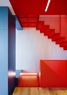 After a Renovation, a Classic San Francisco Victorian Is Now Bursting With Light and Color - Photo 1 of 15 - A perforated-metal staircase in Benjamin Moore's Flame and built-in cabinetry in various shades of blue highlight Fougeron Architecture's bold reinvention of a narrow row house in Noe Valley for a couple and their daughter.
