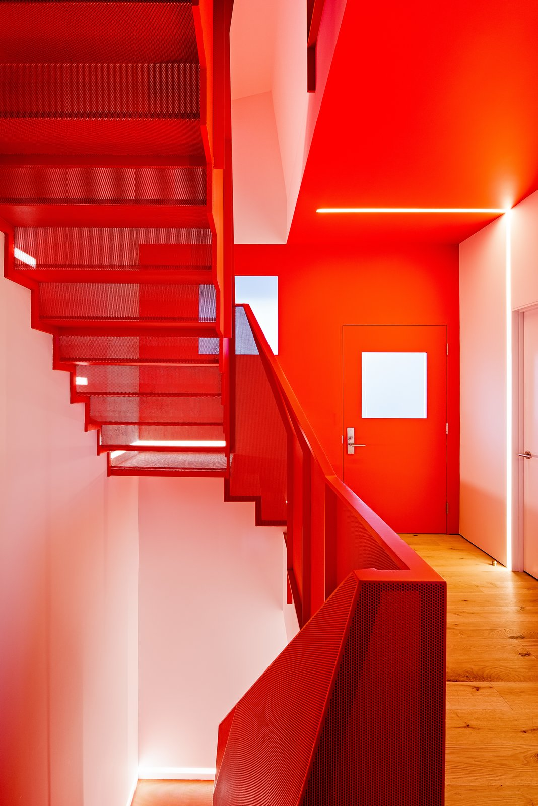 Seen here from the entrance level, the sculptural stair emphasizes the home's verticality and opens up what had been a low-ceilinged, dark interior. Tagged: Staircase, Metal Railing, and Metal Tread.  Photo 9 of 16 in After a Renovation, a Classic San Francisco Victorian Is Now Bursting With Light and Color