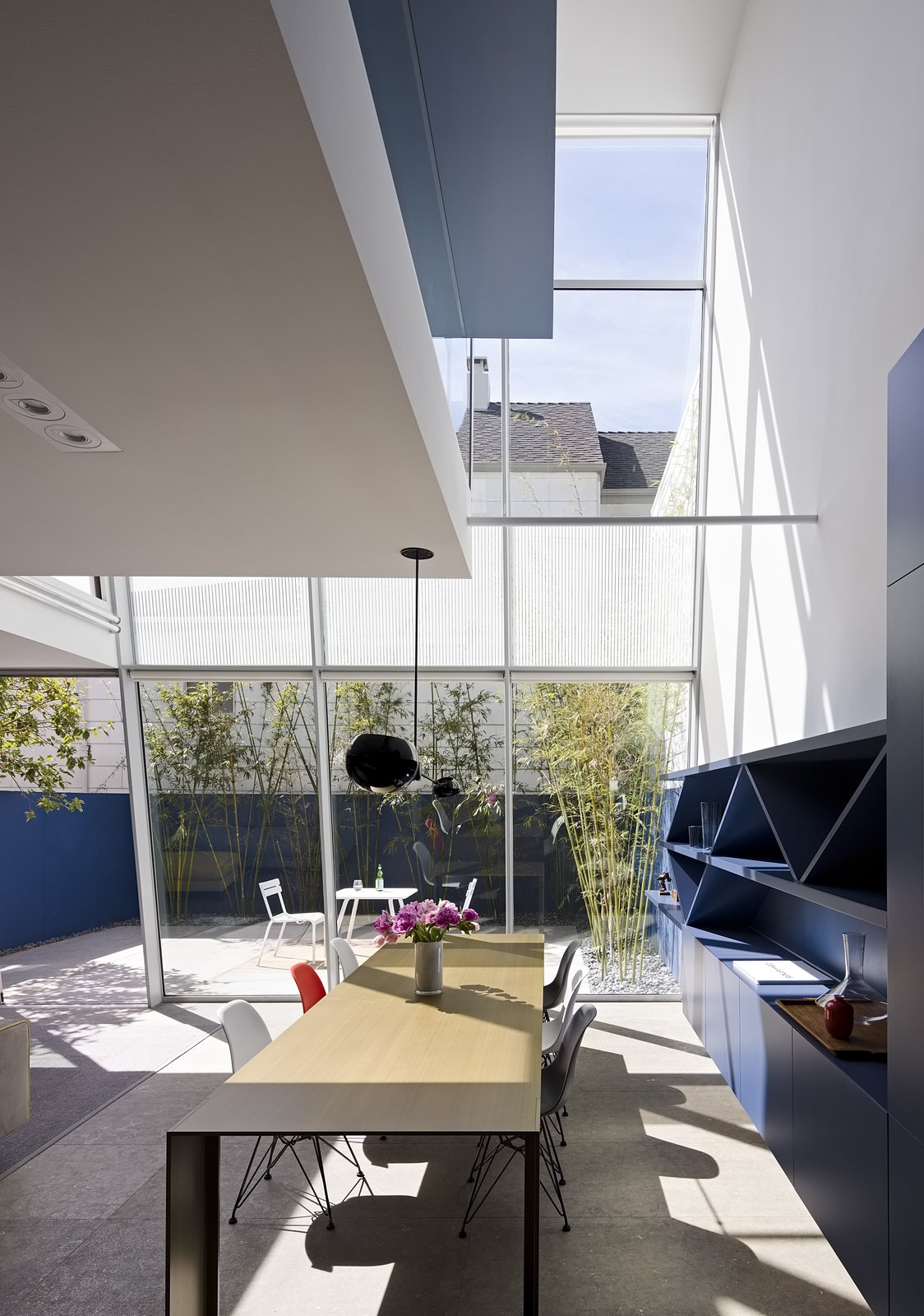"Transforming the rear of the house is something more often found in a high-rise building—a curtain wall that Fougeron and the team hung from the third floor. ""It's actually very complicated to make the field glazing look simple and minimal,"" says the architect. Piero Lissoni's Metallico table for Porro anchors the dining area, while built-in cabinetry offers ample storage. The main living area was created from what was once a basement behind the garage. Limestone floors inside and out unify the living spaces. Tagged: Dining Room, Pendant Lighting, Table, Chair, Limestone Floor, and Shelves.  Photo 12 of 16 in After a Renovation, a Classic San Francisco Victorian Is Now Bursting With Light and Color"