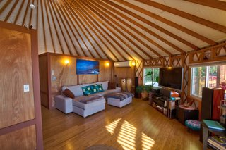 This Santa Barbara Yurt Is the Ultimate Place to Recharge - Photo 4 of 9 - The living room couch converts into an additional bed. The well-appointed entertainment system includes movies, video games, and board games; guests can also play any of the instruments provided.