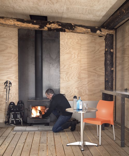 A wood stove completes the enclosed room of the structure. Just two rooms make up The Phoenix: one open room and this enclosed room, home to minimal storage.