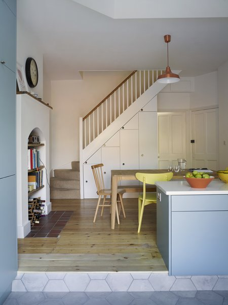 In the dining area, built-in storage was added beneath the staircase. The table is by Ebbe Gehl for John Lewis and the pendant is by Anglepoise.