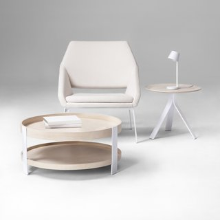"Pictured above, Coffee Table, $149.99; Side Table, $89.99; LED Task Lamp, $49.99; Lounge Chair, $249.99. Thinking of ""a hybrid between a chair with no arms and a chair with arms,"" Deam explains, resulted in this lounge seat, which features steel legs and tall, foam-cushioned sides that comfortably cradle the user."
