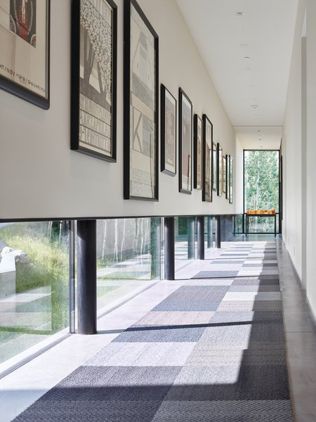 An art gallery was designed with low windows to allow natural light to permeate while protecting the sensitive art from harmful direct sunlight. It is these careful details that, in combination with the striking lineation of the home, create a harmonious alliance of function and design.