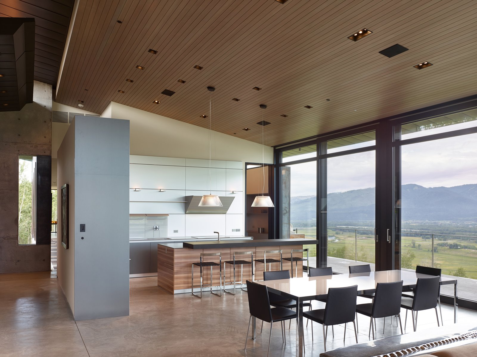 The dining area sits between the open concept kitchen and living room.  Tagged: Kitchen, White Cabinet, Wood Cabinet, Concrete Floor, and Pendant Lighting.  Wyoming Residence by Abramson Teiger Architects