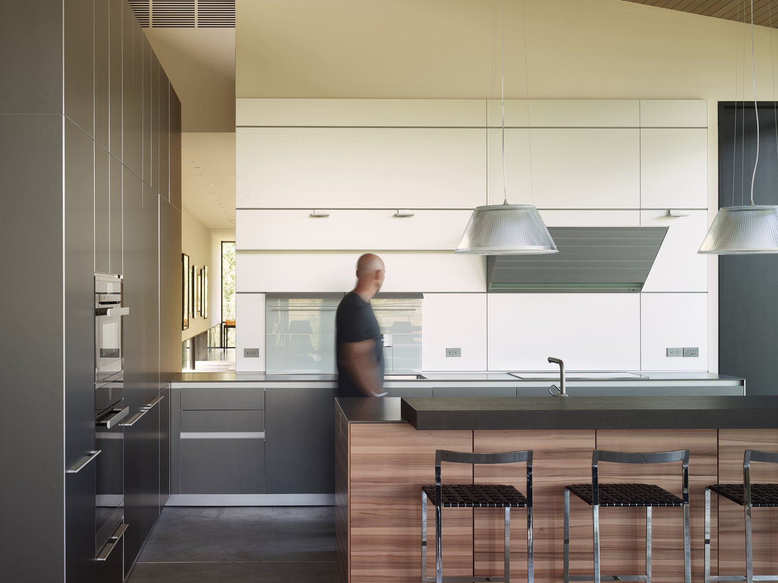 The minimal kitchen design is apportioned with tri-colored cabinets and a clever opening through that overlooks the gallery. Tagged: Kitchen, Wood Cabinet, and White Cabinet.  Wyoming Residence by Abramson Teiger Architects