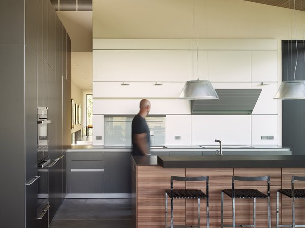 The minimal kitchen design is apportioned with tri-colored cabinets and a clever opening through that overlooks the gallery. Photo 8 of Wyoming Residence modern home