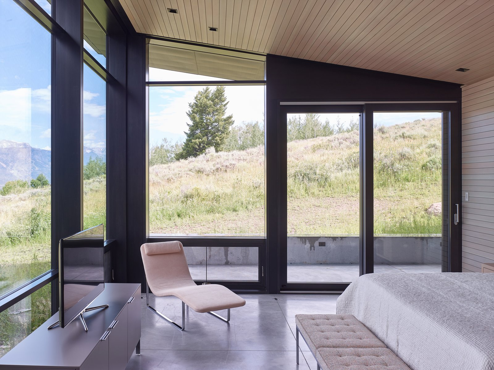 The master bedroom shares in the floor-to-ceiling views, allowing symbiosis with the meadow outside. Tagged: Bedroom, Bed, Chair, Concrete Floor, Bench, and Recessed Lighting.  Wyoming Residence by Abramson Teiger Architects
