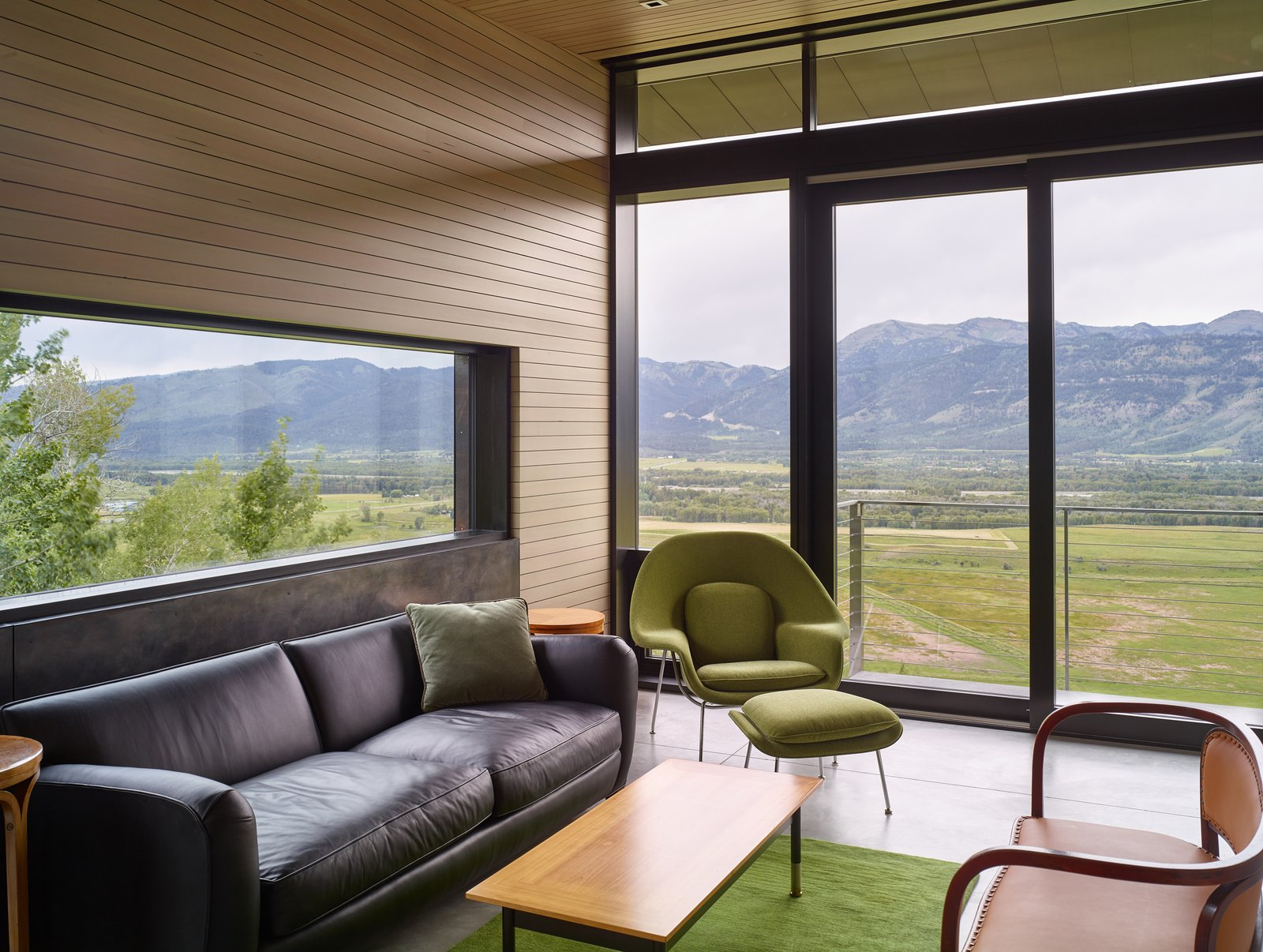 Glass walls open up onto a balcony on the rear of the home.  Tagged: Living Room, Chair, Coffee Tables, and Sofa. Wyoming Residence by Abramson Teiger Architects