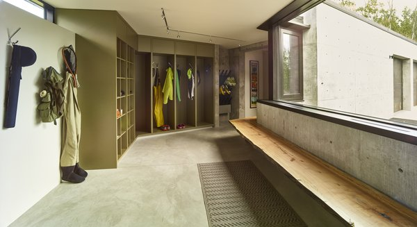 A utilitarian mudroom features built-in storage, ski boot warmers, and a solid wood bench. Photo 14 of Wyoming Residence modern home
