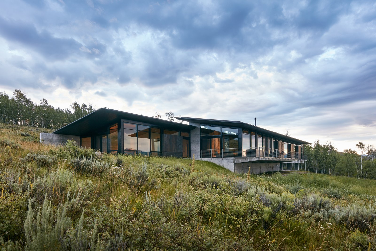 From the entrance, the cantilevered structure wraps around to reveal a comparatively more modest side that bows to the mountains and floats on the meadow. Tagged: Exterior, House, Concrete Siding Material, Green Roof Material, Metal Siding Material, and Shed RoofLine.  Wyoming Residence by Abramson Teiger Architects