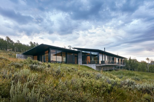From the entrance, the cantilevered structure wraps around to reveal a comparatively more modest side that bows to the mountains and floats on the meadow.