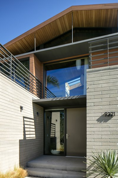 White brick creates a solid base for second-story wood paneling.  Photo 2 of Cohen Residence modern home