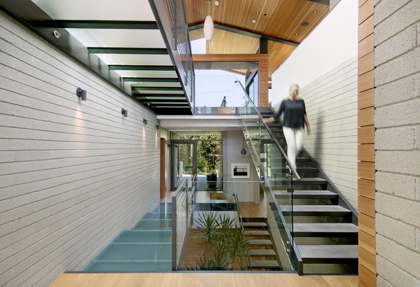 Upon entry, one is greeted by an impressive three-story atrium, accented by steel-framed glass floors and topped with pitched roof ceilings.   Photo 3 of Cohen Residence modern home