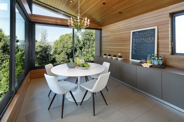 An informal dining area sits just off the kitchen.  Floor-to-ceiling windows on the second-story  paired with wood-paneled walls make the room feel like it is up in the trees.  Photo 7 of Cohen Residence modern home