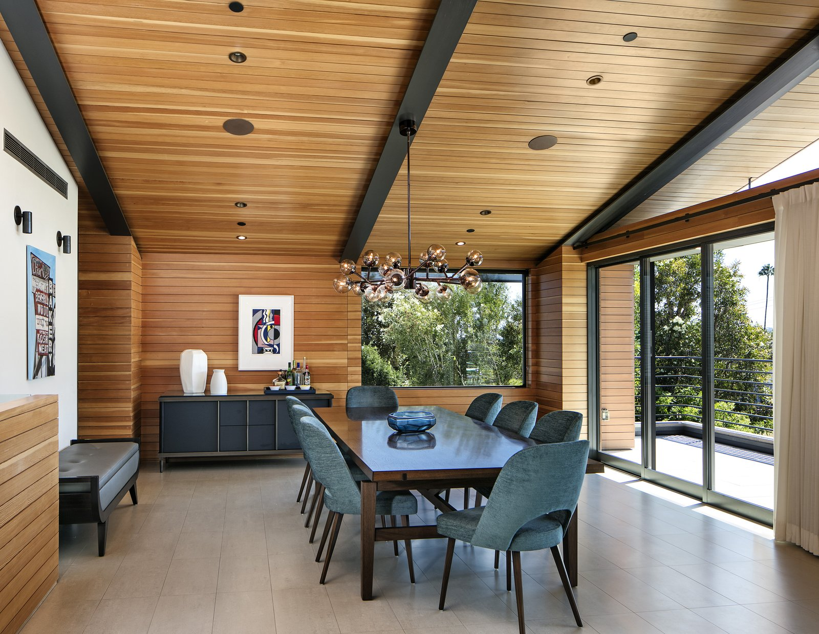 The formal dining area, also on the top level of the home, features Mid-Century furniture and lighting.   Tagged: Dining Room, Table, Chair, Pendant Lighting, Bench, and Storage.  Cohen Residence by Abramson Teiger Architects
