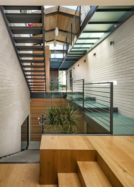 Glass is a prominent material used throughout the residence, seen from the very top of the structure in the form of expansive skylights and layered all the way down through the various levels of walkways.  Not only does this articulate volume, but it also allows the natural light to stream through all levels of the home. Photo 10 of Cohen Residence modern home