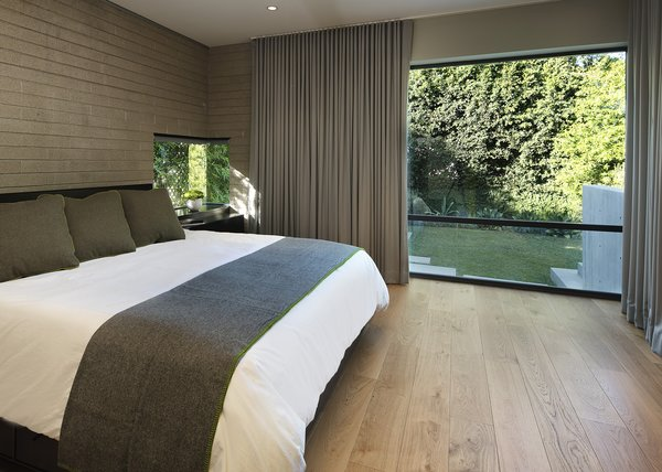 The minimal master bedroom overlooks the back yard.  Photo 11 of Cohen Residence modern home