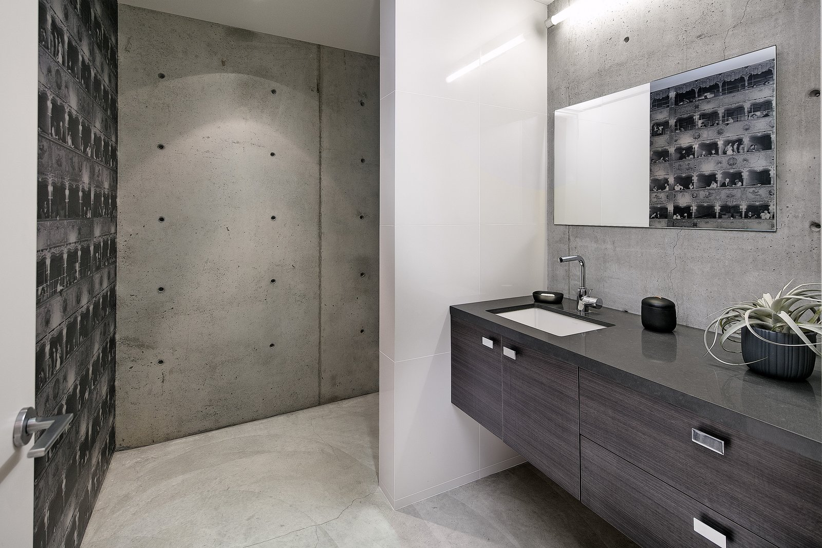 Exposed concrete in the office bathroom compliments the raw materials seen throughout the basement level.   Cohen Residence by Abramson Teiger Architects