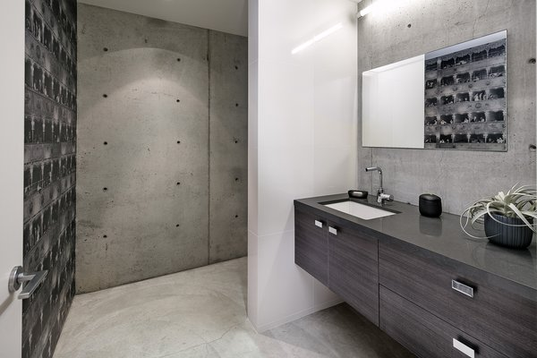 Exposed concrete in the office bathroom compliments the raw materials seen throughout the basement level.  Photo 14 of Cohen Residence modern home