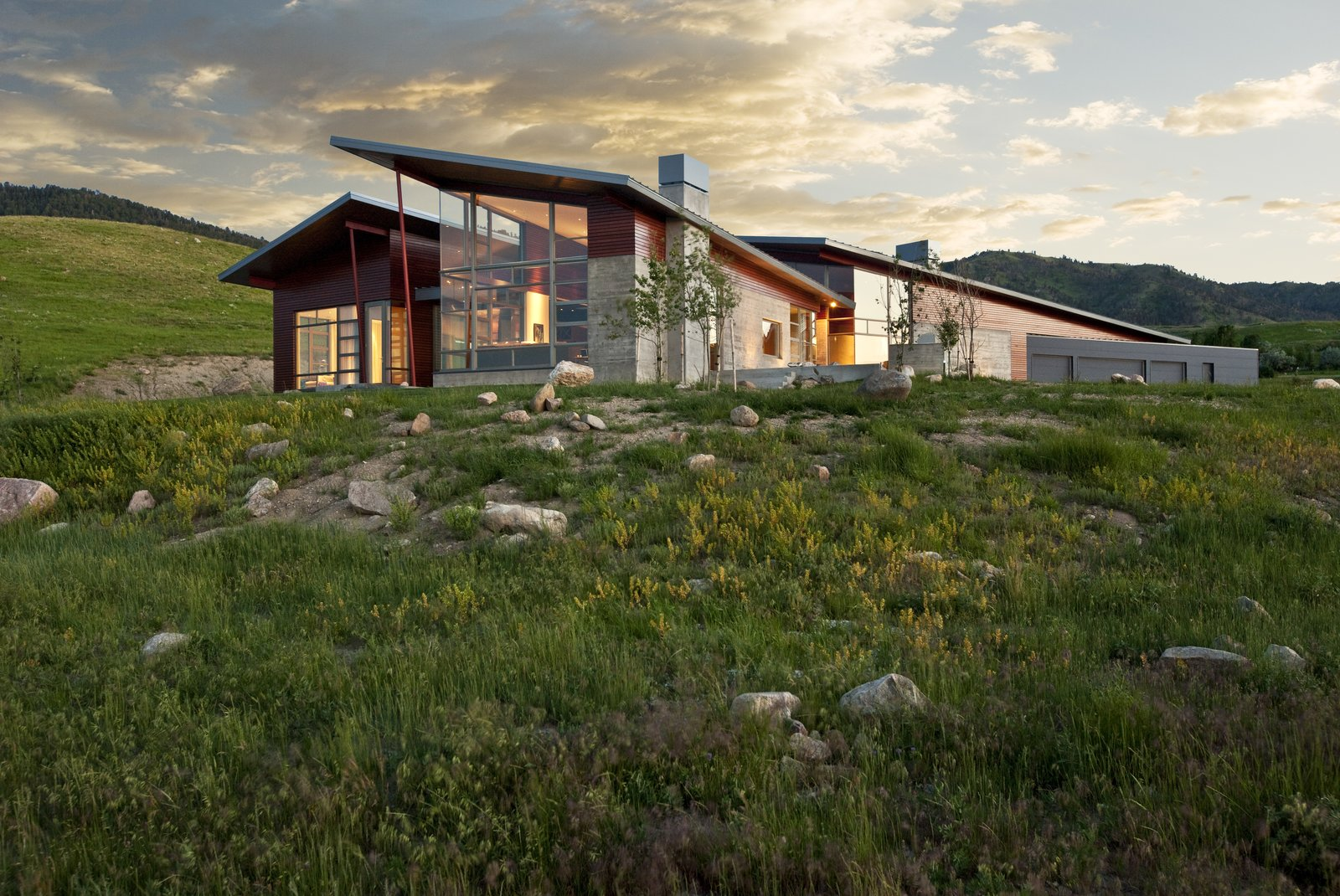 In response to the site's challenges, the architects designed a low-slung structure anchored in concrete, steel and wood that clings to the base of a hillside.  Casper Residence by Abramson Teiger Architects