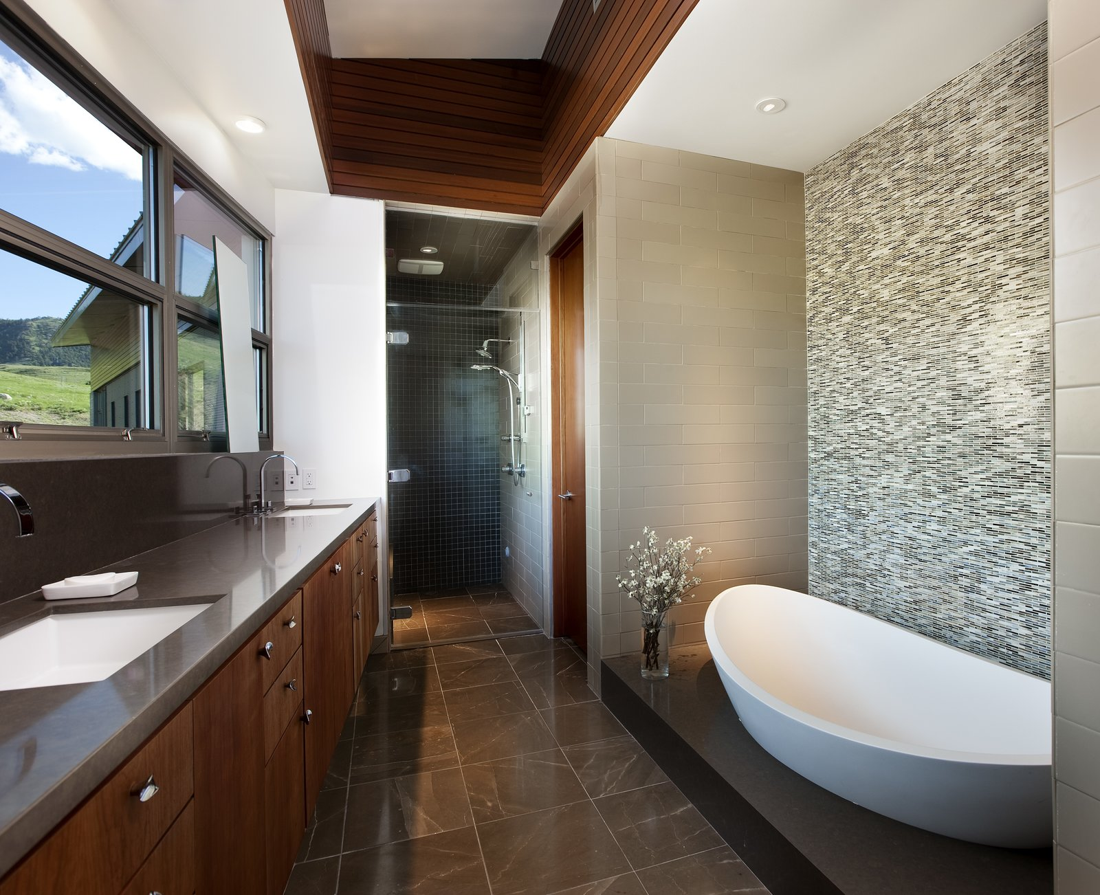 Redwood paneling is also seen in the master bathroom, complimenting the cool-toned mosaic tiles.