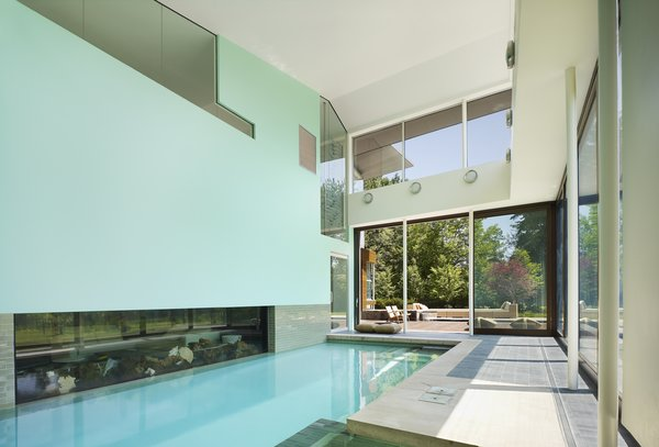 The indoor pool area opens up to the outdoor patio for year round swimming in the cold Toronto climate.  An aquarium is nestled next to the interior pool wall.  Photo 11 of Davis Residence modern home