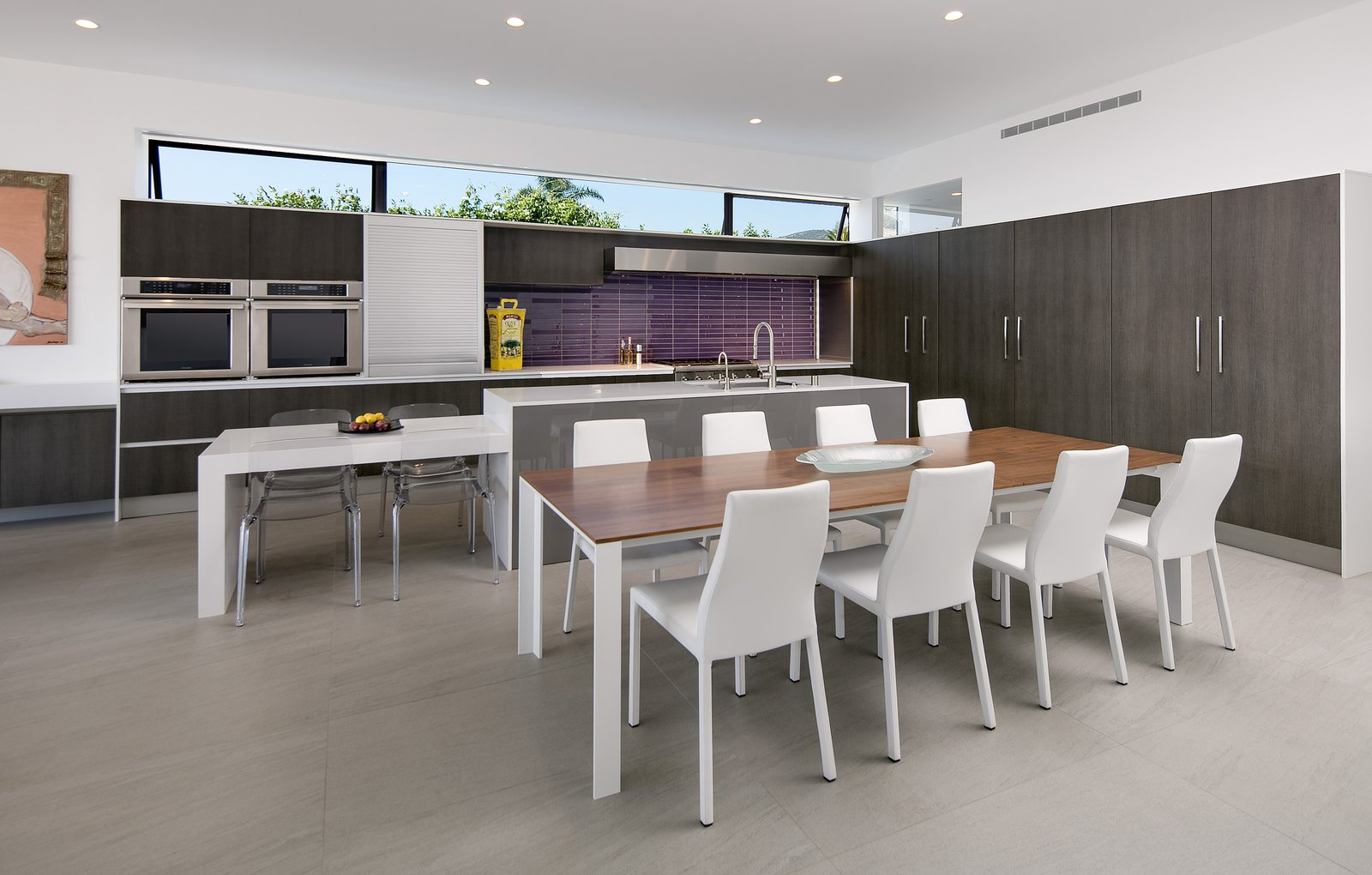 Purple mosaic tile adds a pop of color the the minimal kitchen.
