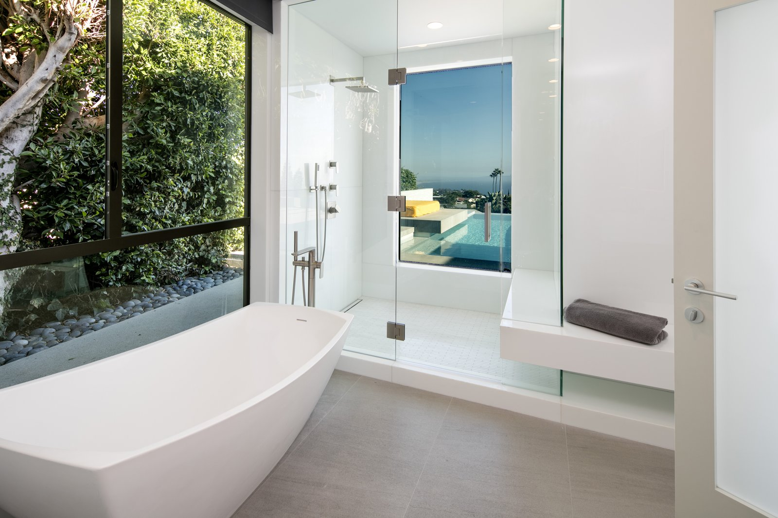 Intimate spaces, such as the master bathroom, are invited to enjoy the view with an extra-large window that overlooks the patio.  Clever details make this functional; the glass becomes opaque when the bathroom lights are on to ensure privacy.  Glenhaven Residence by Abramson Teiger Architects
