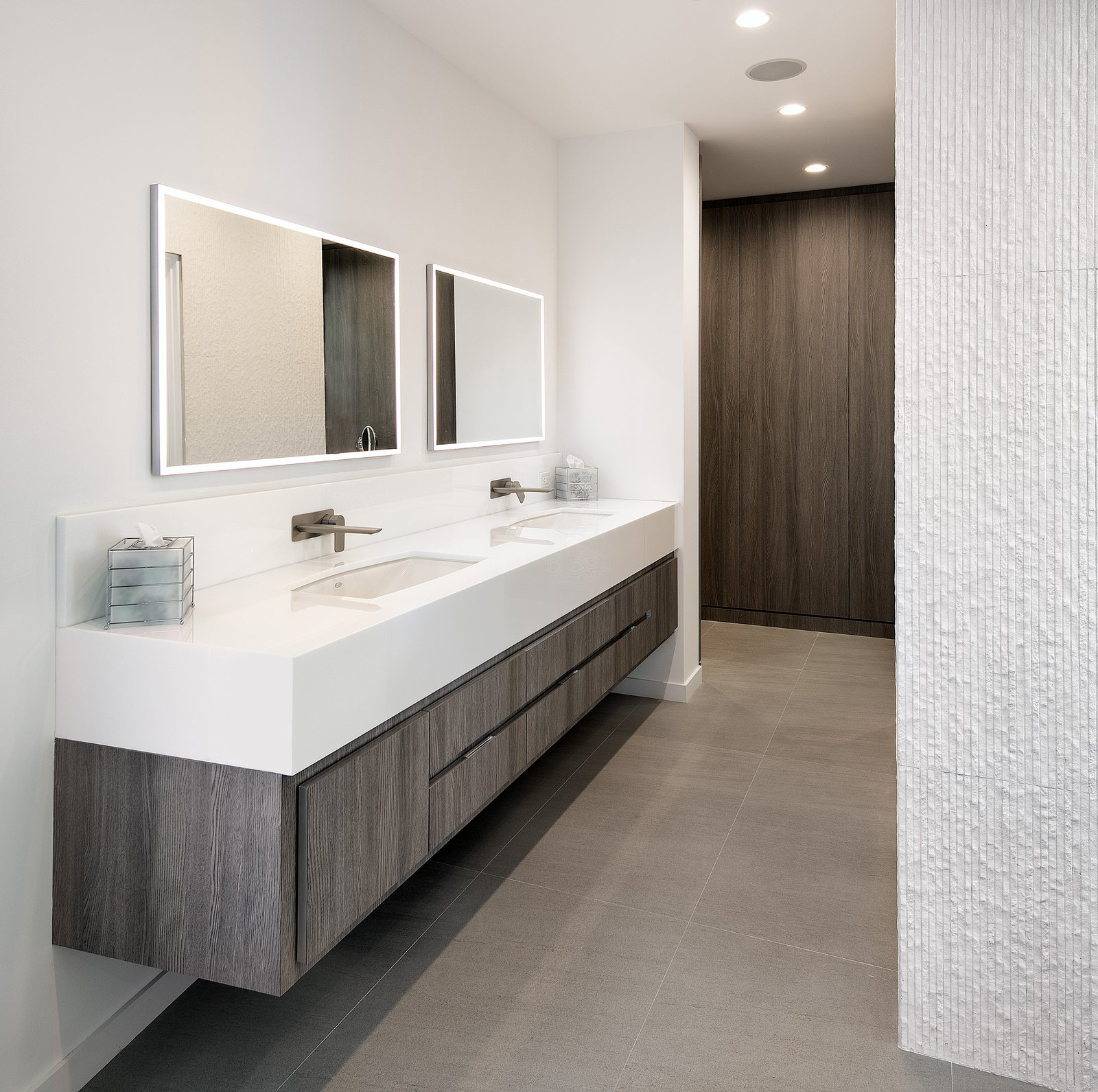 An accent wall with marble mosaic tile adds texture to the sleek bathroom.   Glenhaven Residence by Abramson Teiger Architects