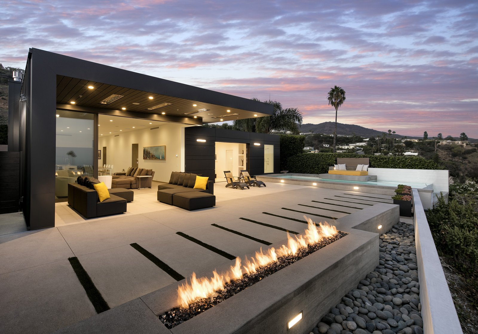 On the patio, an infinity pool overlooks the Pacific Ocean below.  A low profile fire pit is paired with shorter succulents to maintain a direct view.    Glenhaven Residence by Abramson Teiger Architects