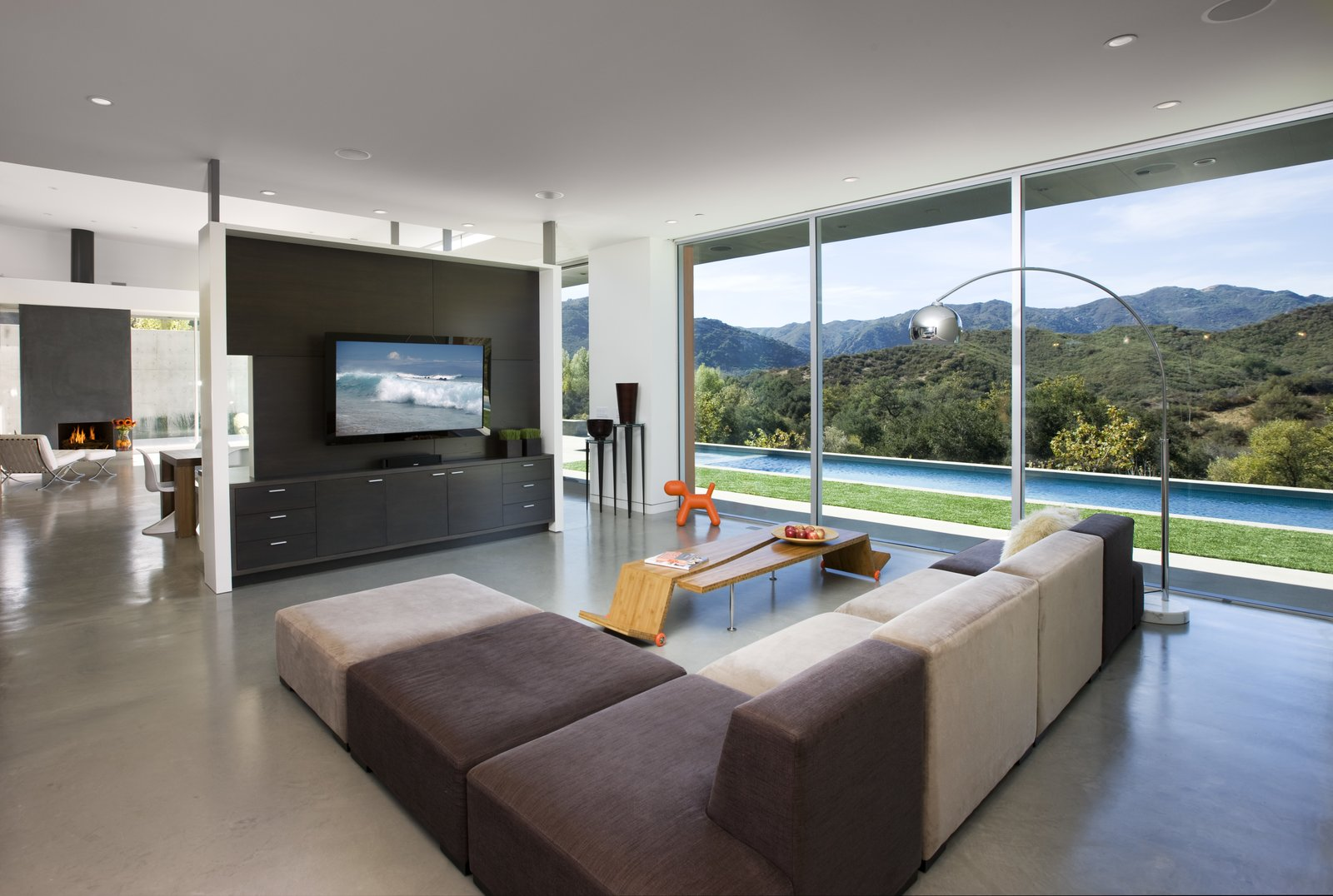 The open concept living room overlooks the pool outside and the mountains on the horizon. Interior walls never fully meet the ceiling, to keep a loft-like open floor plan.   Lima Residence by Abramson Teiger Architects