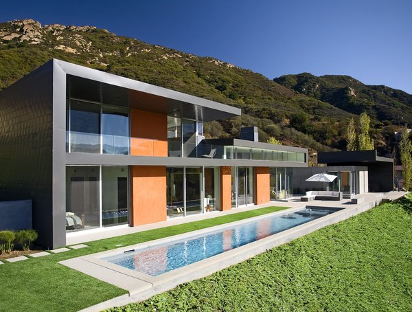 A narrow pool is nestled into the back yard next to an outdoor living area.  Photo 9 of Lima Residence modern home