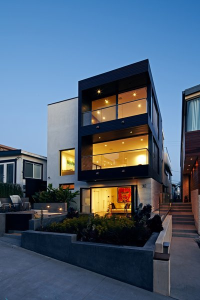 The front façade was redesigned with large openings that create a connection to the ocean views.  Accordion style glass doors were installed on the lower floor to form an indoor-outdoor space with the front garden.  The exterior palette is a subtle mix of smooth trowel stucco and honed limestone, emboldened with dark stained mahogany siding. Photo  of Perrin Residence modern home