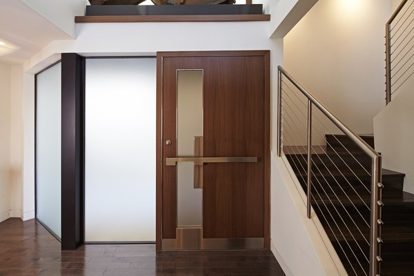 The public entry sequence pulls you through the front garden, leading to the main entry which sits on the side of the home.  A custom designed walnut and stainless steel door opens into a two-story foyer.  Photo 2 of Perrin Residence modern home